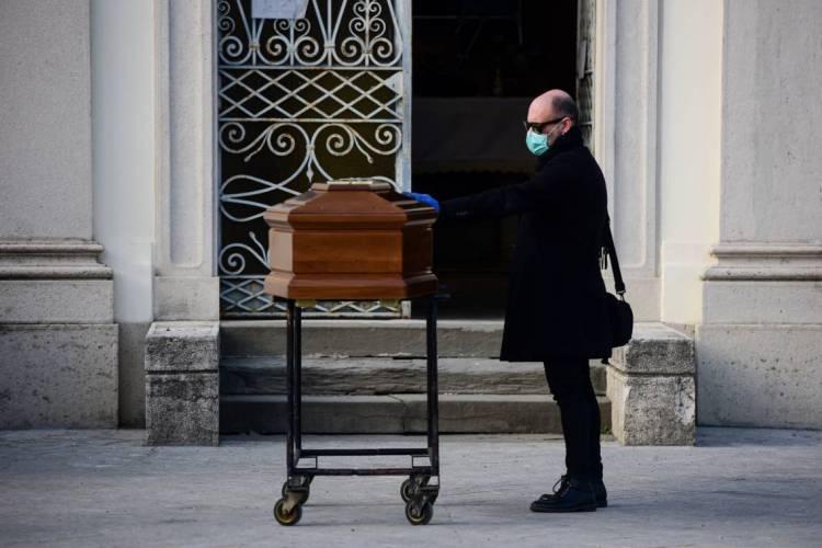 Italia em 20 de março de 2020, Um homem toca o caixão de sua mãe durante um funeral no cemitério fechado de Seriate, perto de Bergamo, Lombardia, durante o bloqueio do país com o objetivo de impedir a propagação da pandemia de Covid-19 (Foto: Piero Cruciatti / AFP)