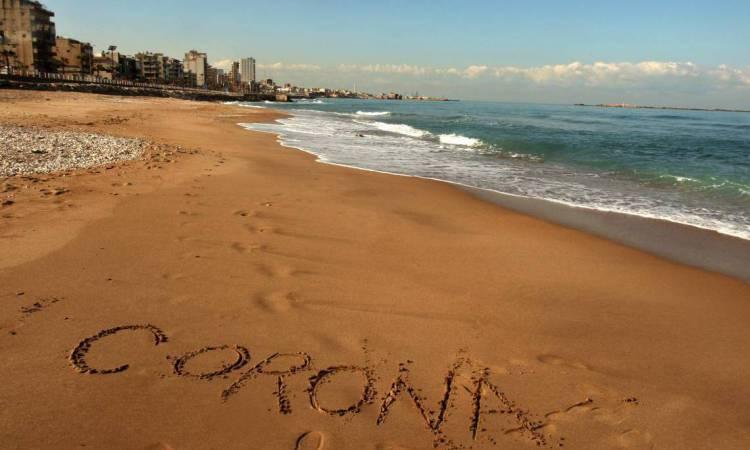 Líbano em 22 de março de 2020, A foto mostra a palavra Corona escrita na areia da praia na cidade de Saida, no sul do Líbano, em meio à disseminação do coronavírus no país.  (Foto de Mahmoud ZAYYAT / AFP)