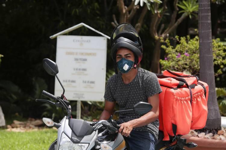 Motoqueiro usa máscara para realizar entregas de comida