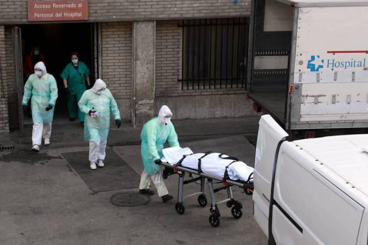 Paramédicos carregam corpo de paciente morto por Covid-19 em Madrid, Espanha (Foto: Oscar Del Pozo/AFP)