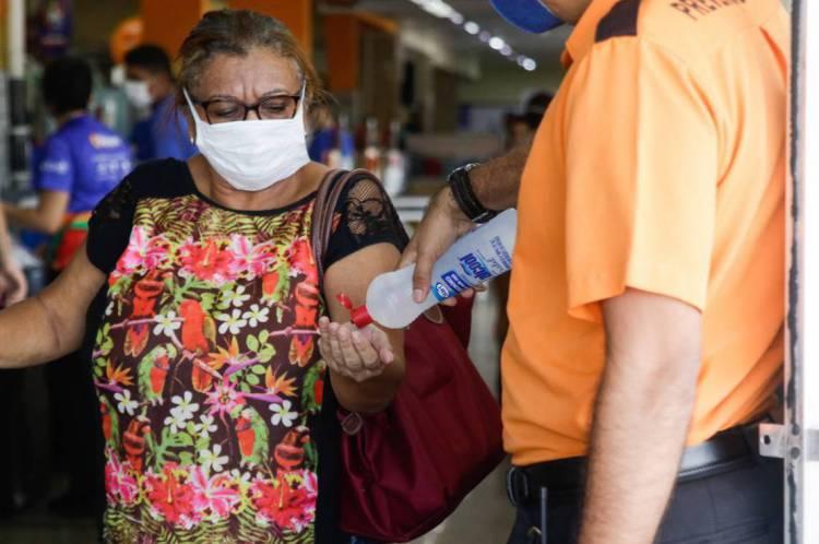 Funcionário do supermercado oferecendo álcool gel na entrada para prevenção do Coronavírus. (Foto: Beatriz Boblitz/ O POVO)