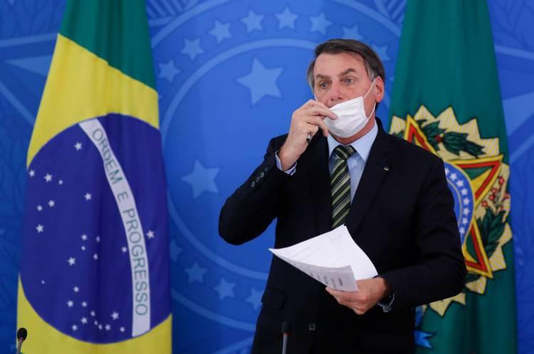 Brasília, em 18 de março de 2020. O presidente brasileiro Jair Bolsonaro tira a máscara durante uma conferência de imprensa sobre a pandemia de coronavírus COVID-19 no Palácio do Planalto. (Foto de Sergio LIMA / AFP)