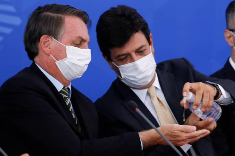 Jair Bolsonaro (E) e o então ministro da Saúde, Luiz Henrique Mandetta (Foto: Sergio LIMA / AFP)