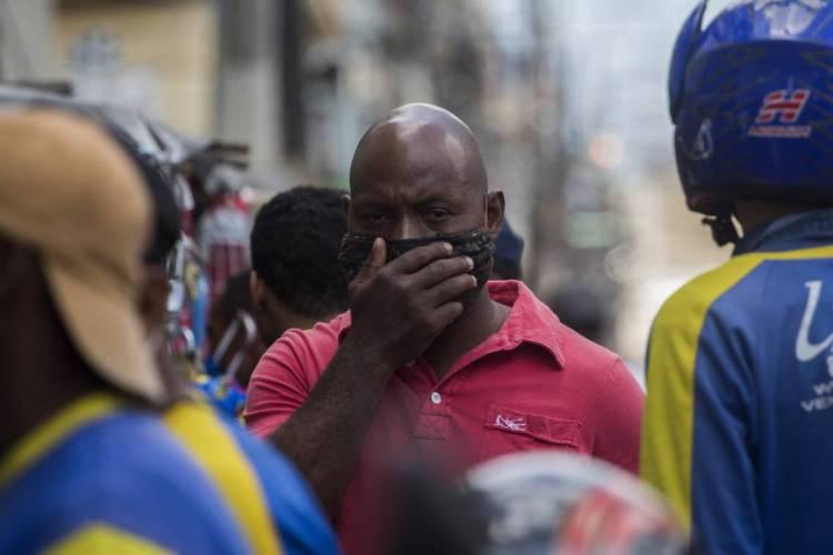 Homem na República Dominicana improvisa máscara para proteger o rosto (Foto: Erika SANTELICES / AFP)