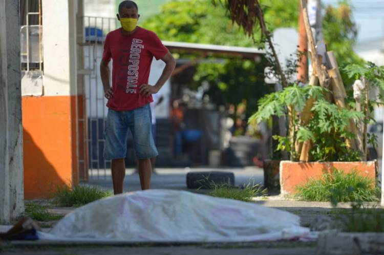 Um homem olha para um corpo que foi deixado por três dias fora de uma clínica em Guayaquil, Equador
