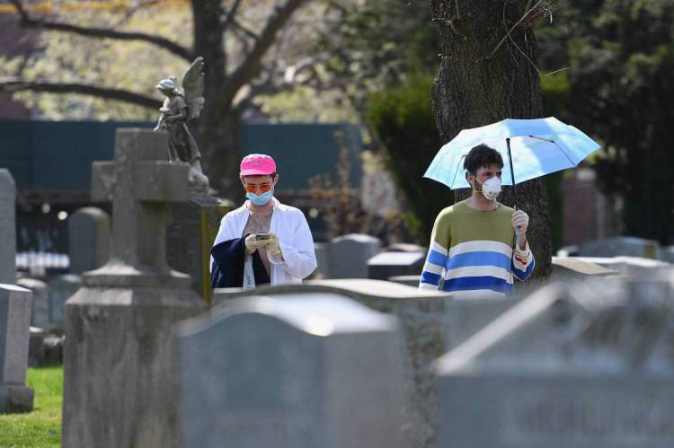 Nova York em 7 de abril de 2020, Pessoas que usam máscaras atravessam um cemitério  no Brooklyn, Nova York. Devido a coronavirus