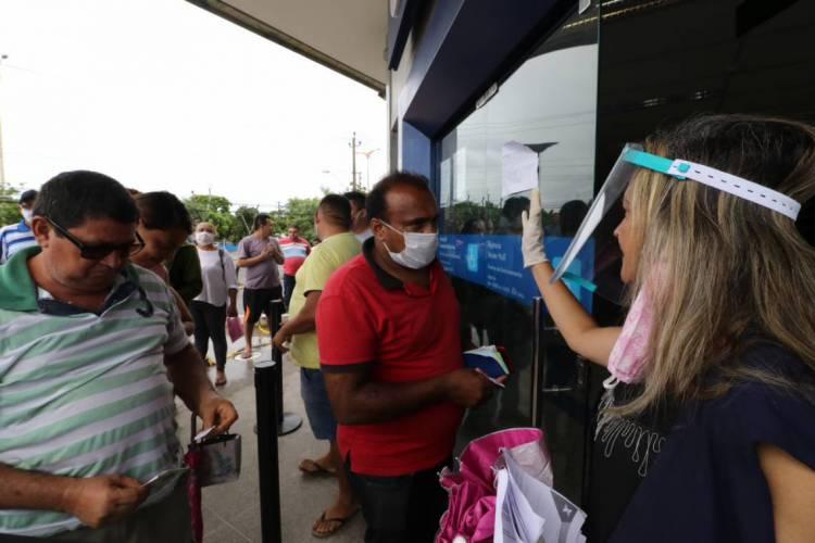 FORTALEZA, CE, BRASIL, 15.04.2020: Operação da PM para conscientizar população sobre o Coronavírus nas filas para receber o auxílio, na Caixa Econômica Federal da Av. Mister Hull.   (Foto: Fabio Lima)