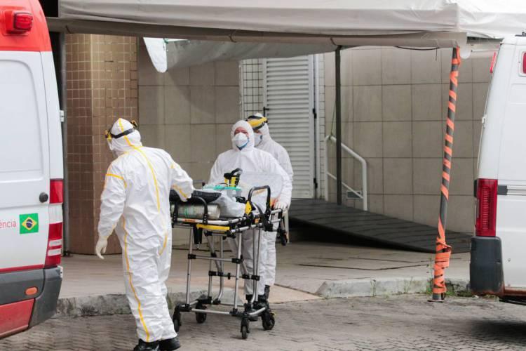 FORTALEZA-CE, BRASIL, 16-04-2020: Profissionais de saúde vestidos com EPIs passam álcool em gel na ambulância antes de sair do Hospital Leonardo Da Vinci para buscar uma pessoa com suspeita de Covid-19 em Fortaleza (Foto: JÚLIO CAESAR)