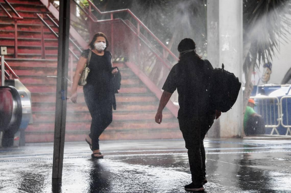 Pessoas recebem spray de solução desinfectante na entrada de estação de trem em Osasco, interior de  São Paulo (Foto: Nelson Almeida / AFP)
