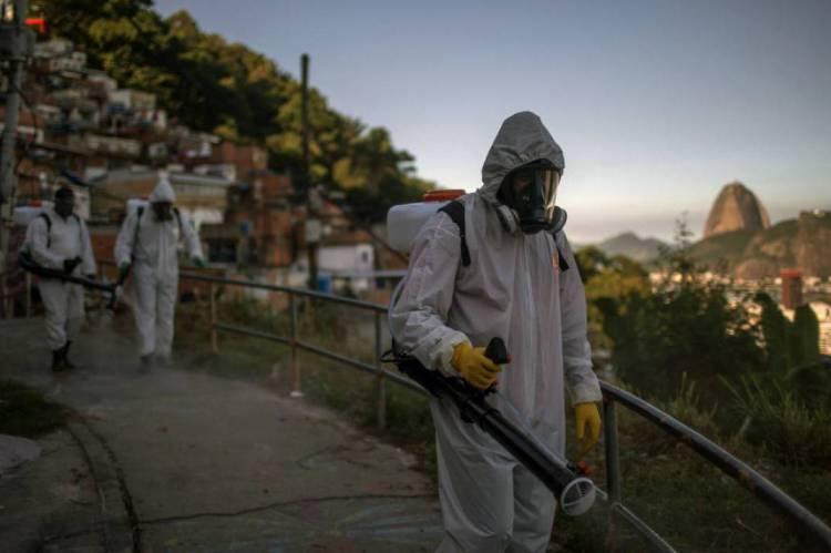 Agentes desinfetam uma estrada na favela de Santa Marta, no Rio de Janeiro, durante a pandemia de coronavírus COVID-19 em 20 de abril de 2020.