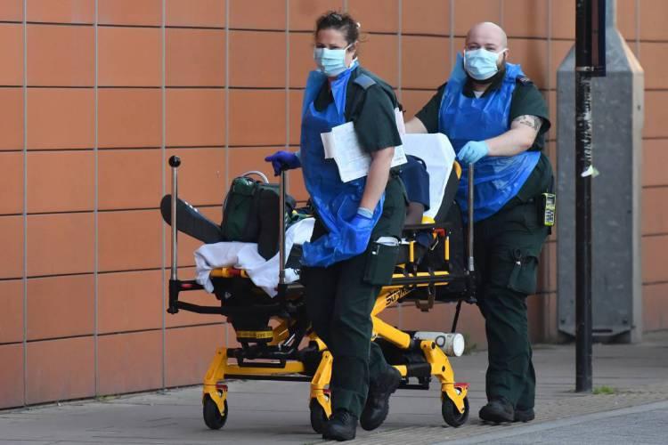 Paramédicos transportam um paciente para o Royal London Hospital, no leste de Londres, durante a nova pandemia de coronavírus  (Foto: Justin Tallis -AFP)