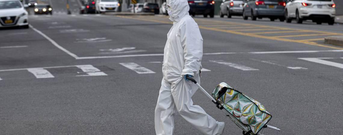 Mulher com trajes de proteção caminha pelas ruas do bairro Queens, em Nova York (Foto:  Johannes EISELE / AFP)