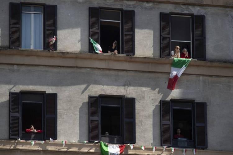 Moradores do distrito de Garbatella, em Roma, balançam a bandeira italiana e cantam