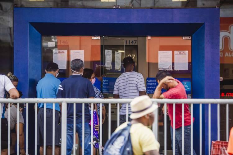 FORTALEZA, CE, BRASIL, 27-04-2020: Caixa Economica Federal na Avenida Duque de Caxias com Rua Floriano Peixoto, com muitas pessoas para receber  o beneficio do Governo, com muita chuva e aglomeração., em epoca de COVID-19 (Foto: Aurelio Alves/O POVO) (Foto: Aurelio Alves/O POVO)