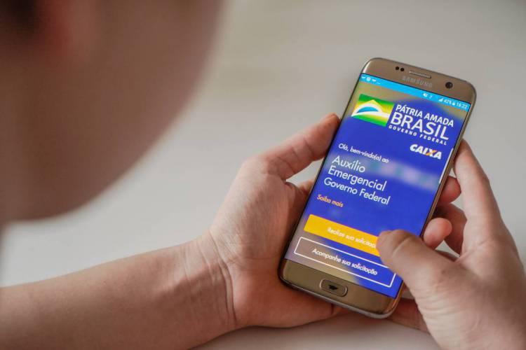 FORTALEZA-CE, BRASIL, 27-04-2020: Personagem manipulando celular com aplicativo de auxílio emergencial da Caixa Econômica Federal.  ( Foto: Júlio Caesar / O Povo) (Foto: JULIO CAESAR)