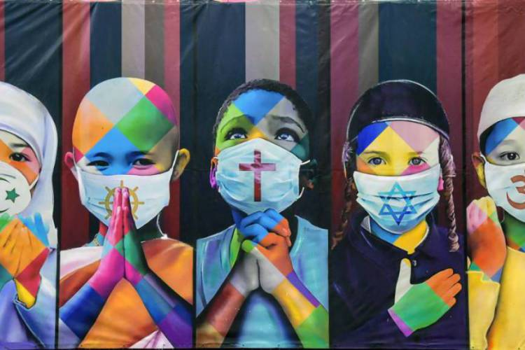 """Vista do trabalho recente do artista Eduardo Kobra """"Coexistência"""", que mostra crianças usando máscaras faciais devido ao novo coronavírus, Covid-19, portando símbolos de diferentes religiões (da esquerda para a direita) Islã, budismo, cristianismo, judaísmo e hinduísmo (Foto: NELSON ALMEIDA / AFP)"""
