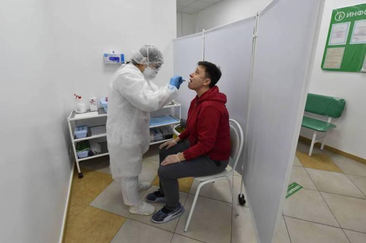 Equipe médica tira uma amostra de saliva de um homem em uma instalação de testes de Covid-19 em Moscou neste sábado, 2 de maio de 2020