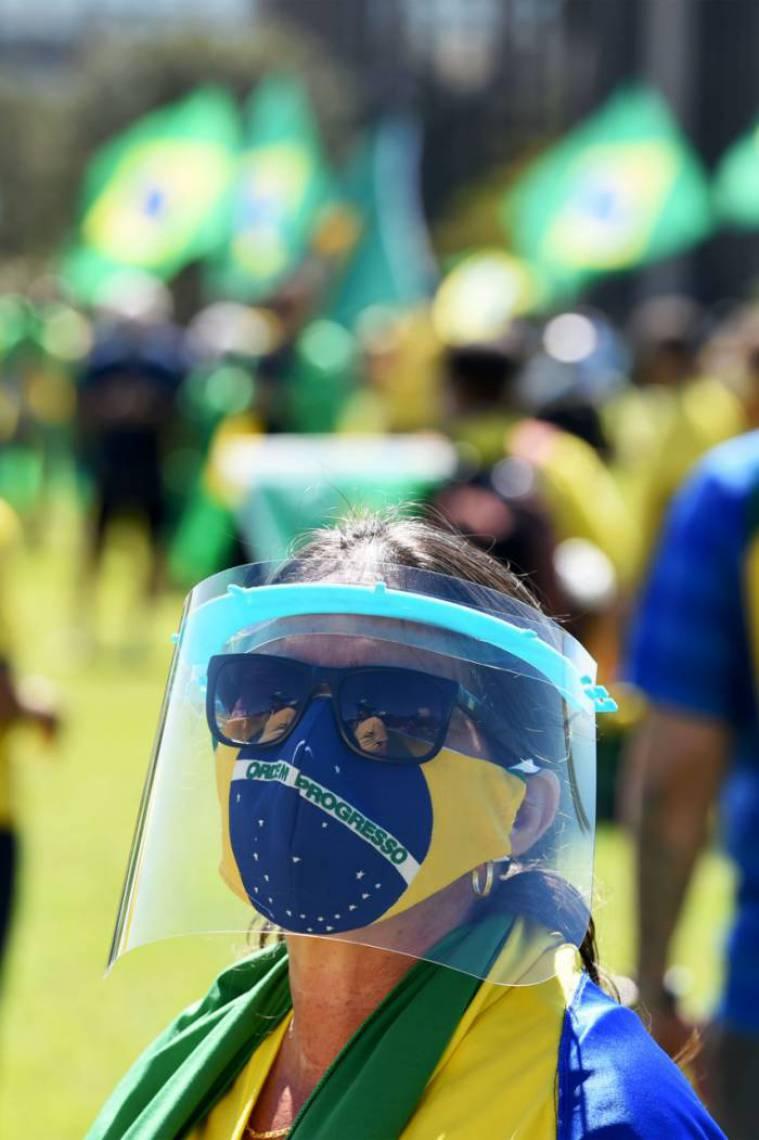 Mulher usa Equipamento de Proteção Individual (EPI) em manifestação