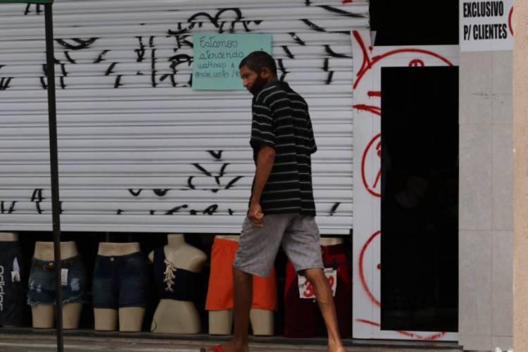 Parte do comércio funciona com portas semi-abertas na Messejana, neste sábado, 09/05/2020 (Foto: Fabio Lima/O POVO)