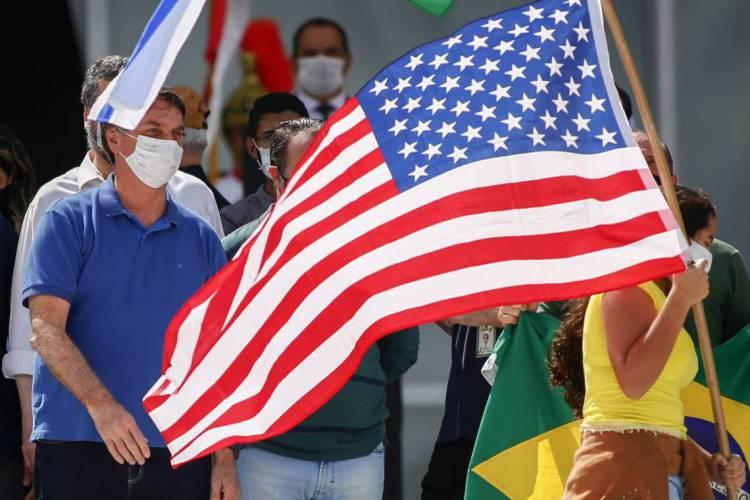 O presidente brasileiro Jair Bolsonaro (E) se une a apoiadores lisonjeiros de uma bandeira dos EUA durante um comício em Brasília em 17 de maio de 2020, em meio à nova pandemia de coronavírus. - O número de mortos no Brasil no COVID-19 ultrapassou 15.000 no sábado, mostraram dados oficiais, enquanto seu número de infecções superou 230.000, tornando-o o país com o quarto maior número de casos no mundo. (Foto: Sergio LIMA / AFP).. (Foto: SÉRGIO LIMA / AFP)