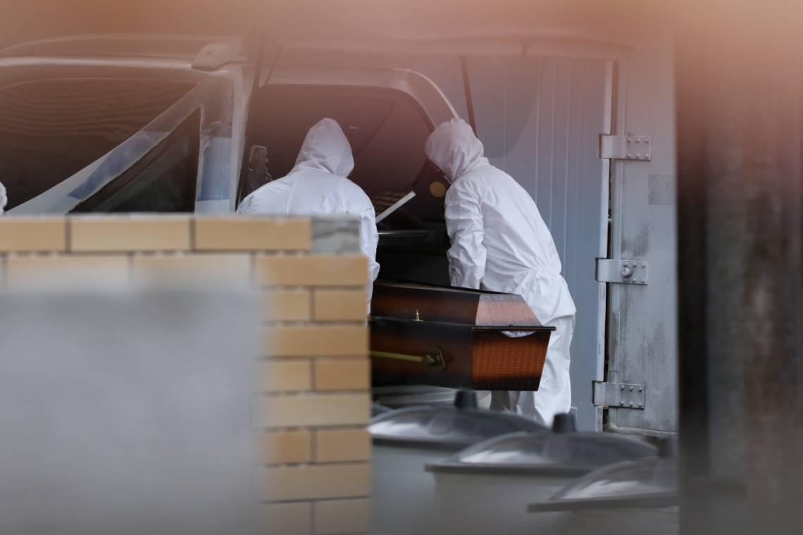 Homens com equipamento de proteção retiram corpo em caixão do contêiner do IJF 2 (Fotos: Fabio Lima/O POVO)