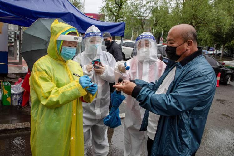 Voluntários vestindo roupas de proteção verificam a temperatura corporal de um residente na entrada de uma área residencial em Jilin, na província de Jilin, nordeste da China (Foto: AFP)