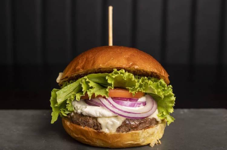Cheeseburguer clássico do Hey Joe Food N Bar, feito de um burger, molho da casa, cebola roxa, alface, tomate e mussarela no pão brioche