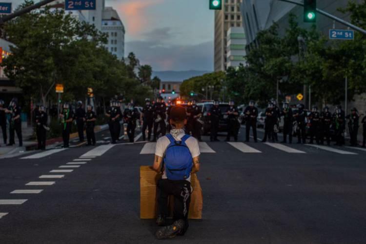 Um manifestante se ajoelha em frente à força policial, em ato de protesto em Los Angeles (Foto: Apu GOMES / AFP)
