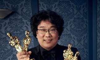 O cineasta Bong Joon-Ho segura suas quatro estatuetas por