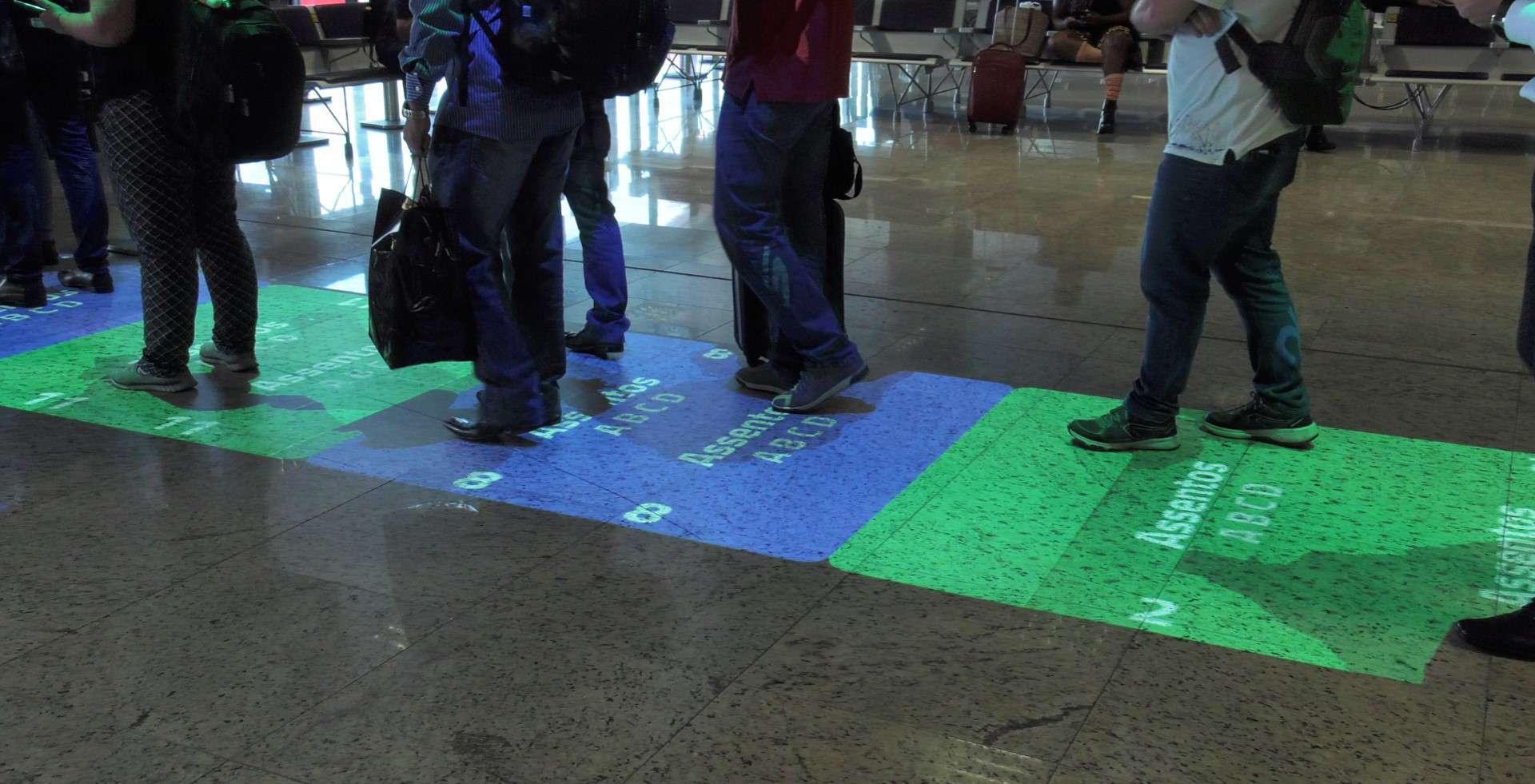 Através da utilização de realidade aumentada, projetores formam um tapete virtual móvel, que convida as pessoas a se posicionarem na fila na hora de embarcar
