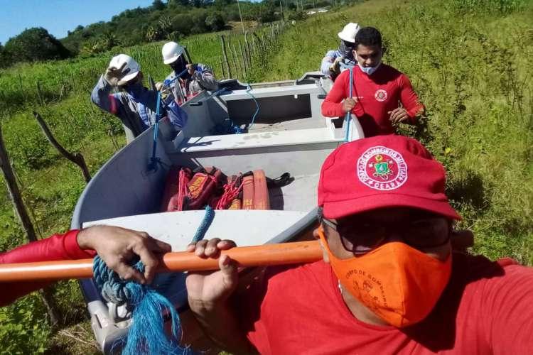 Equipe do Corpo de Bombeiros conduz funcionários da Enel sobre as águas de um riacho. Foto: Ascom/Corpo de Bombeiros (Foto: Ascom/Corpo de Bombeiros)