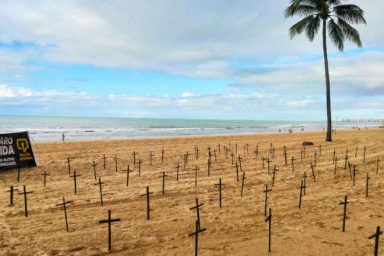 Ativistas colocaram 180 cruzes nas areias da praia de Boa Viagem, no Recife, em homenagem às vítimas do novo coronavírus e em protesto contra Bolsonaro (Foto: Bruno Campos / JC Imagem)