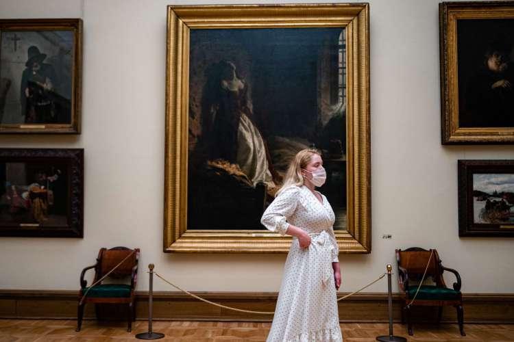 Visitante usa máscara protetora enquanto olha para as pinturas penduradas na galeria estatal Tretyakov, em Moscou. Galeria foi aberta após a flexibilização das medidas contra a propagação da doença por coronavírus (Foto: DIMITAR DILKOFF / AFP)