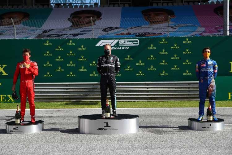 O piloto monegasco da Ferrari, Charles Leclerc; o piloto finlandês da Mercedes Valtteri Bottas; e o britânico da McLaren, Lando Norris, comemoram no pódio após a corrida do Grande Prêmio da Áustria de F1 (Foto: AFP)