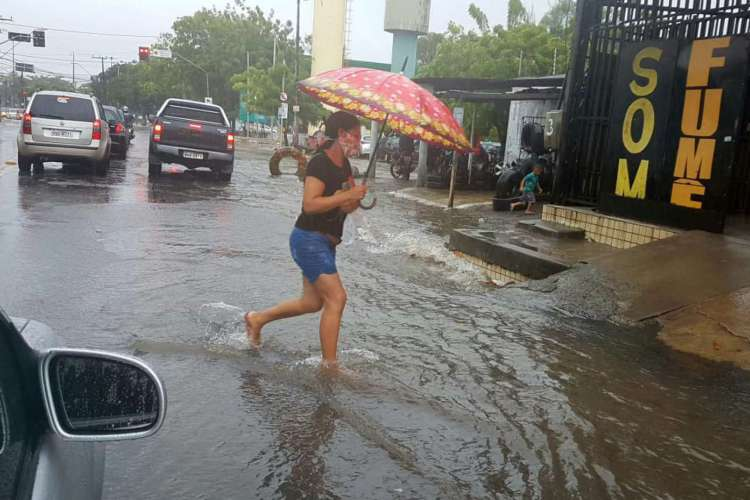Chuva em Fortaleza nesta segunda-feira, 6. Pedestre atravessa a avenida José Bastos (Foto: Francisco Fontenele)