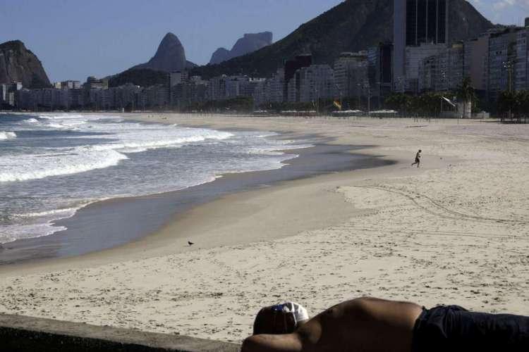 Um homem de máscara protetora relaxa na calçada da praia do Leme durante o surto de doença de coronavírus (COVID-19), no Rio de Janeiro, Brasil, 9 de maio de 2020. REUTERS / Ricardo Moraes (Foto: REUTERS / Ricardo Moraes)