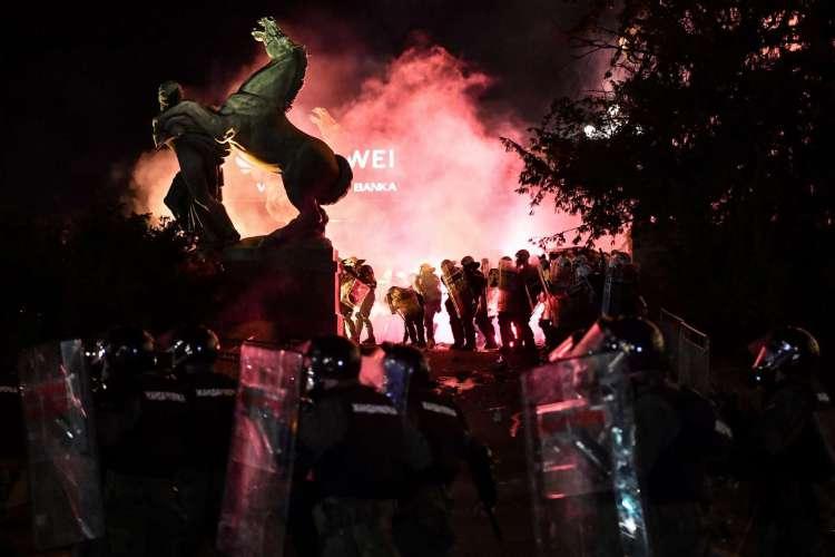 A polícia está em fumaça de gás lacrimogêneo do lado de fora do prédio da Assembléia Nacional em Belgrado, em 10 de julho de 2020, durante confrontos com manifestantes em uma manifestação contra o toque de recolher anunciado para combater o ressurgimento das infecções por COVID-19 (novo coronavírus). - A Sérvia anunciou um número recorde de mortes por coronavírus por um único dia em 10 de julho, quando o governo reagiu aos protestos contra o tratamento da pandemia. (Foto de ANDREJ ISAKOVIC / AFP) (Foto: ANDREJ ISAKOVIC / AFP)
