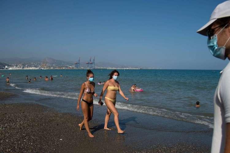 Pessoas usando máscara caminhando pela praia de La Misericordia, em Malaga, em 22 de julho de 2020 (Foto: AFP)