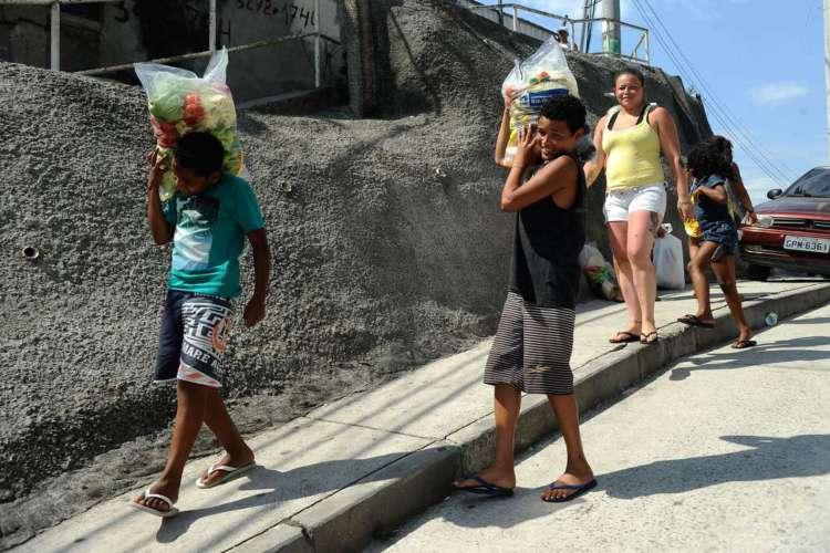 Moradores do Complexo do Alemão recebem doações do Banco de Alimentos da Ceasa, em cerca de 200 sacas com 8 kg contendo frutas, legumes e verduras (Fernando Frazão/Agência Brasil) (Foto: Fernando Frazão/Agência Brasil)