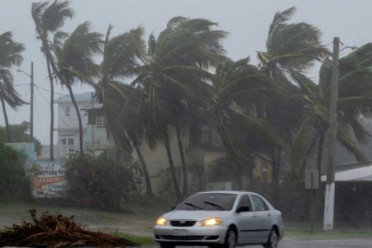 Carro passa por estrada no momento em que a tempestade tropical Laura arrasa Guayama, em Porto Rico (Foto: AFP)