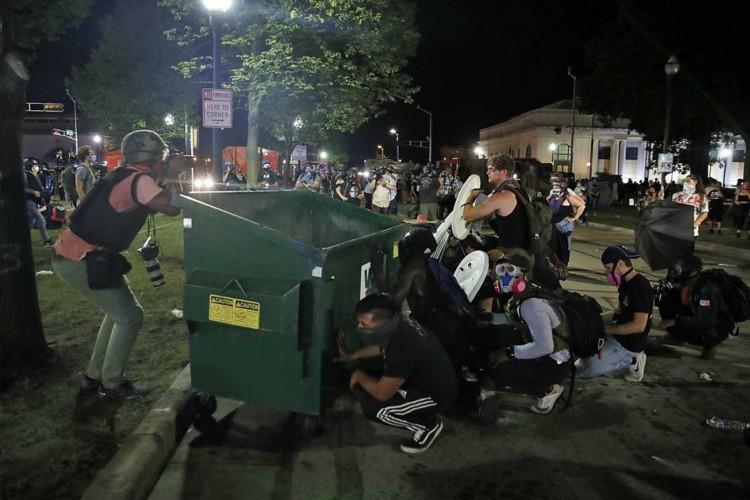 Manifestantes se protegem atrás de uma lixeira em Kenosha, Wisconsin, enquanto a polícia atira gás lacrimogênio (Foto:  Kamil Krzaczynski / AFP Photo)