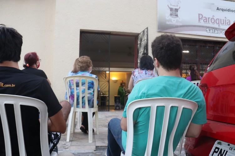 Fiéis acompanham transmissão de missa online na porta da igreja. (Foto: Leonardo Maia/O POVO)