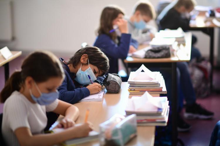 Alunos usando máscaras protetoras escrevem durante uma aula na escola secundária Françoise-Giroud em Vincennes, a leste de Paris, em 1º de setembro de 202 (Foto: AFP)