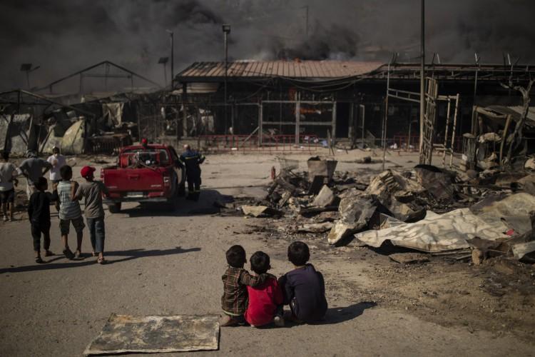 Crianças sentam-se no campo queimado de Moria na ilha de Lesbos depois que um grande incêndio estourou, em 9 de setembro de 2020 (Foto: AFP)