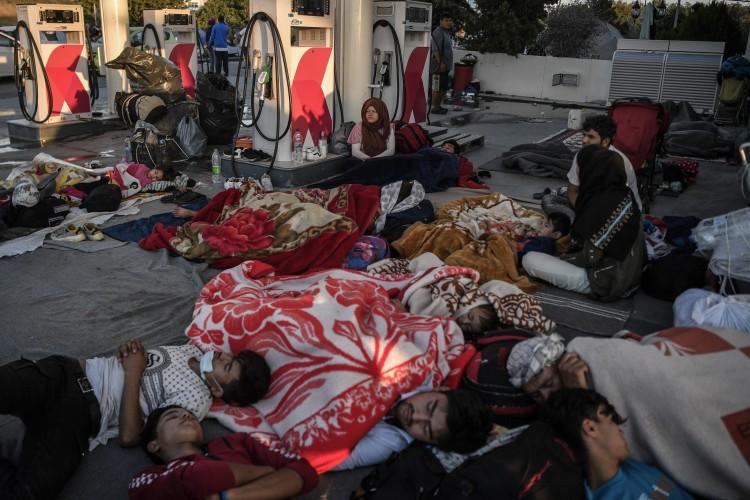Imigrantes sem-teto e refugiados dormem, em 11 de setembro de 2020, num posto de gasolina depois que um incêndio destruiu o maior campo de refugiados de Moria da Grécia na ilha de Lesbos (Foto: AFP)