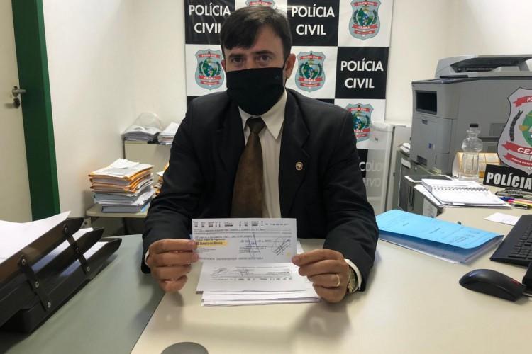 Delegado adjunto da Delegacia de Defraudações e Falsificações (DDF), Carlos Teófilo, apresenta o cheque falso no valor de quase R$ 50 milhões (Foto: Foto: Angélica Feitosa/O POVO)