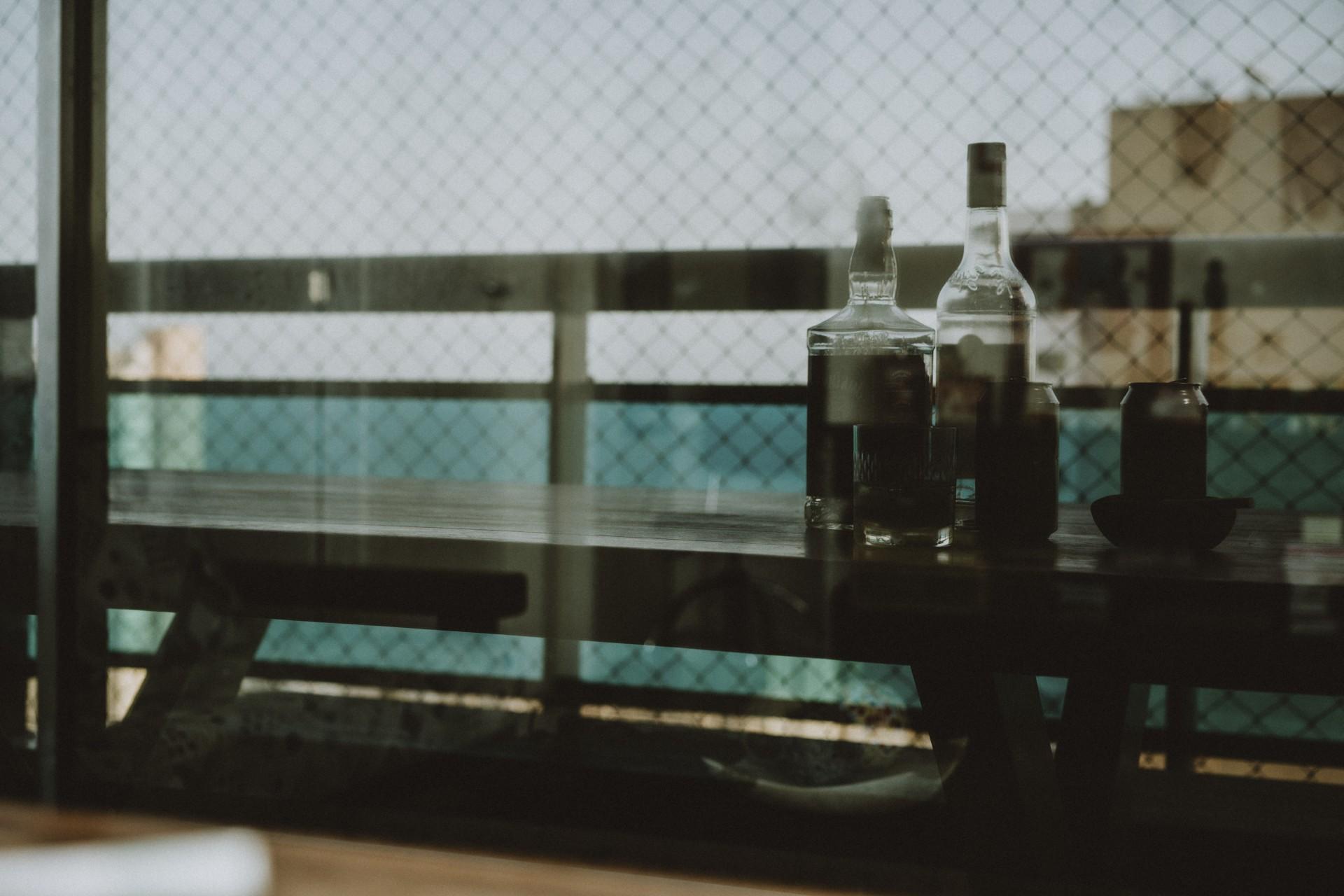 FORTALEZA - CE, BRASIL, 22-09-2020: Reflexo de garrafas de bebida e cinzeiro com cigarro sobre a mesa. Aumento do uso de drogas ilícitas e lícitas durante a pandemia. Ciência e Saúde.  (Foto: Júlio Caesar / O Povo)