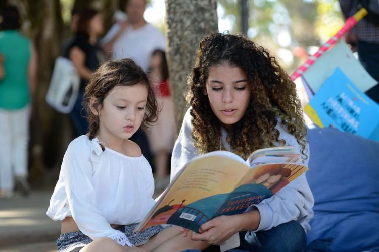 Paraty (RJ) - Adulto lê livro para criança na Praça da Matriz, palco da Flipinha (Tomaz Silva/Agência Brasil) (Foto: Tomaz Silva/Agência Brasil)