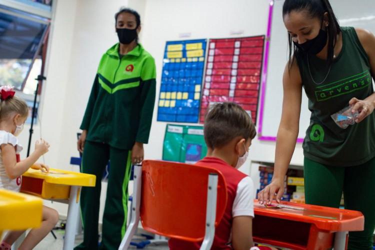 Volta às aulas durante a pandemia em uma escola particular do Distrito Federal. Crianças com máscaras estão sentadas em cadeiras próximas de professoes em uma sala de aula