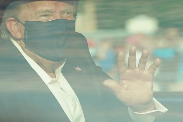 Trump dentro do carro, usando máscara, acenando para seus seguidores (Foto: ALEX EDELMAN / AFP)